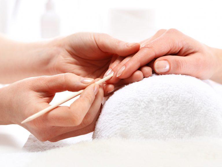 Manicure, odpychanie skórek, kobieta u kosmetyczki