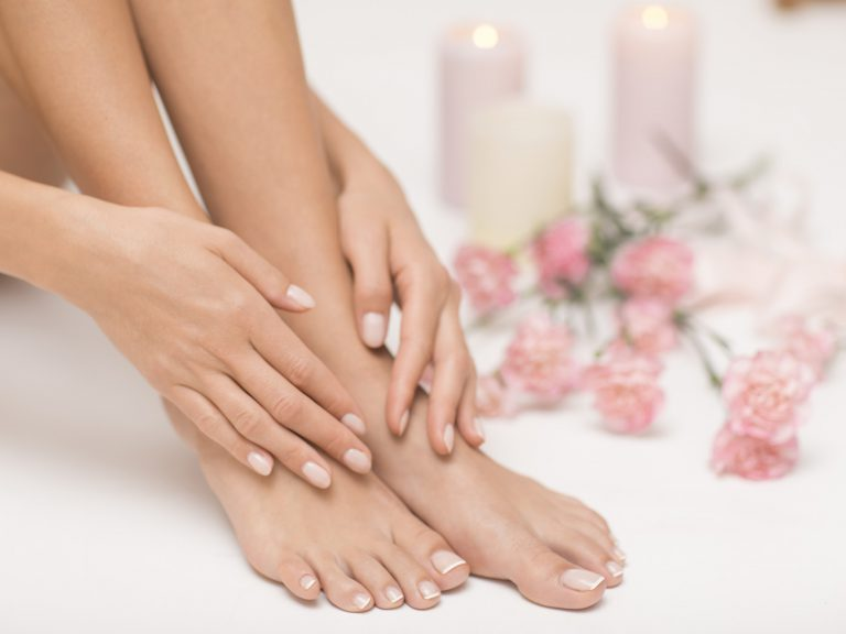 The picture of ideal done manicure and pedicure. Female hands an